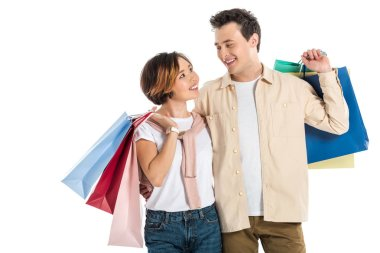 Smiling couple looking at each other and carrying shopping bags isolated on white stock vector