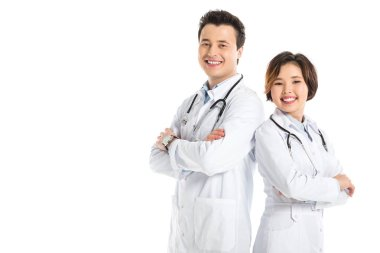 female doctor and male doctor with crossed arms looking at camera and smiling isolated on white