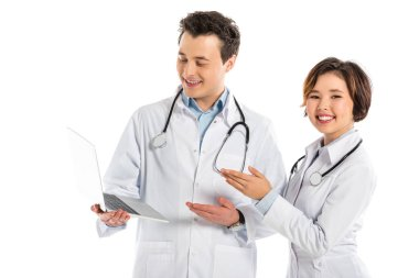 smiling female and male doctors using laptop isolated on white