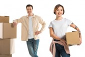 Photo smiling couple looking at camera and holding cardboard boxes isolated on white, moving to new house concept