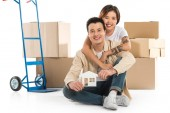 Fotografie couple hugging and holding house model with cardboard boxes on background, moving to new house concept