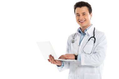Smiling male doctor holding laptop and looking at camera isolated on white stock vector