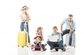 glückliche Familie sitzt auf dem Gepäckstück und sieht auf der Landkarte isoliert auf weiß
