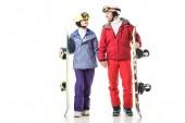 usmívající se pár v lyžařských kompletů holding snowboardy a pohledu na sebe izolované na bílém
