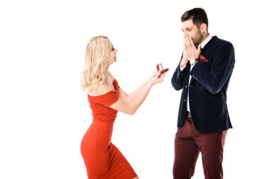 Attractive woman proposing surprised boyfriend with ring isolated on white