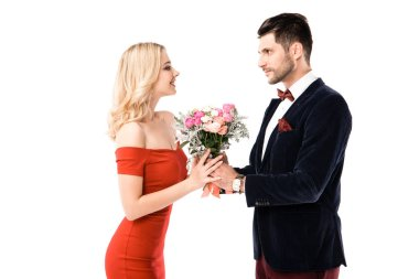 Side view of handsome man giving flowers to girlfriend isolated on white
