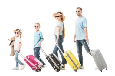Happy family walking with colourful luggage and smiling isolated on white