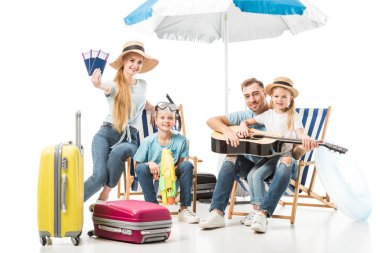 Cheerful family sitting on deck chairs with baggage on white