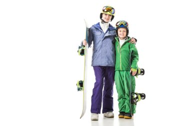 young mom and preteen son in ski suits with snowboards hugging isolated on white