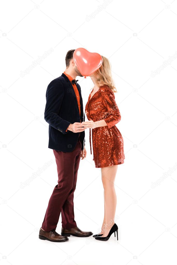 Attractive couple holding hands and kissing while hiding faces behind red balloon isolated on white stock vector