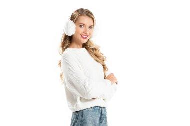 smiling girl in winter earmuffs posing with crossed arms isolated on white