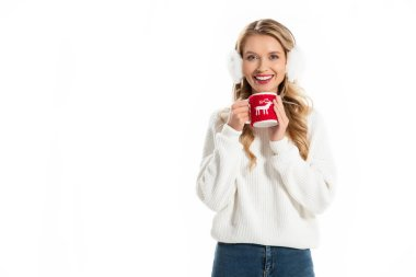 Smiling woman in winter earmuffs holding cup with hot drink isolated on white stock vector