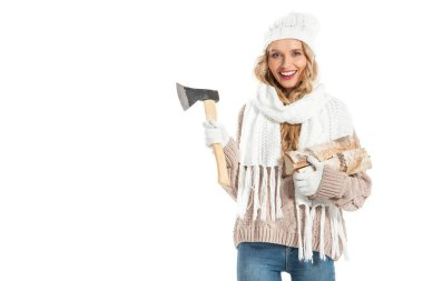 Smiling girl in warm clothes holding ax and firewood isolated on white