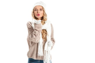 Attractive young woman in warm knitted clothes blowing air kiss and looking at camera isolated on white