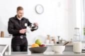 láhev mléka, mísa ovoce na kuchyňském stole a policejní důstojník na pozadí