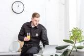 Mladý policista sedí na stole s džusem a pomocí přenosného počítače v kuchyni