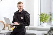 pohledný policista s úsměvem a pomocí přenosného počítače v kuchyni