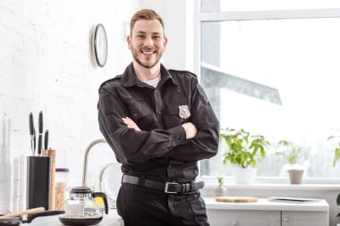 smiling police officer with crossed arms standing next to kitchen table