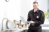 Photo Smiling police officer standing with laptop at kitchen