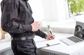 Ausgeschnittene Ansicht eines Polizisten, der Kaffee trinkt und in Notizbuch am Küchentisch schreibt