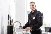 Pohledný policista mytí nádobí v kuchyni