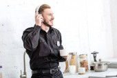 Photo Handsome policeman drinking coffee and listening to music with headphones at kitchen