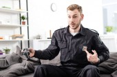 Photo surprised police officer playing video game and pointing at police badge