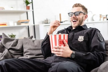 Happy policeman in 3d glasses sitting on couch, eating popcorn and watching movie