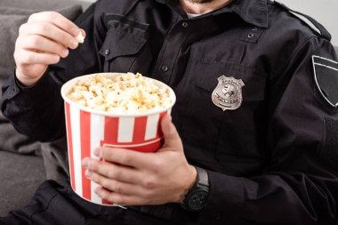 Cropped view of policeman sitting on couch and eating popcorn stock vector