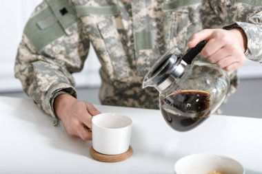 Cropped view of man in camouflage uniform pouring coffee in cup from kettle stock vector