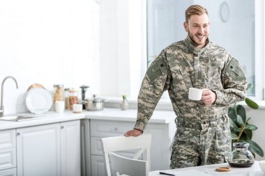 Smiling army soldier holding cup of coffee in kitchen stock vector