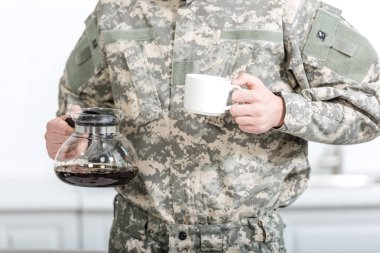 Partial view of army soldier holding cup of coffee and pot in kitchen stock vector