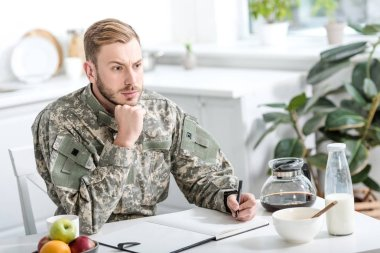 Pensive army soldier sitting at kitchen table and writing while having breakfast stock vector