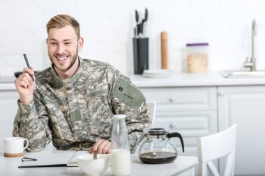 Smiling army soldier sitting at kitchen table with pen and notebook while having breakfast stock vector