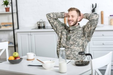 Smiling army soldier sitting at kitchen table with hands on head while having breakfast stock vector