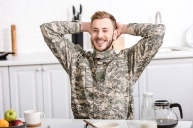 Smiling army soldier sitting at kitchen table with hands on head and having breakfast stock vector