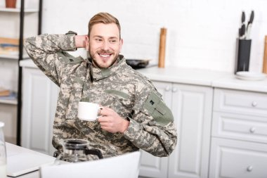 Army soldier sitting at kitchen table with cup of coffee stock vector