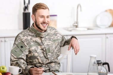 Smiling army soldier sitting at kitchen table while having breakfast stock vector