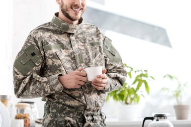 Cropped view of army soldier holding cup of coffee in kitchen stock vector