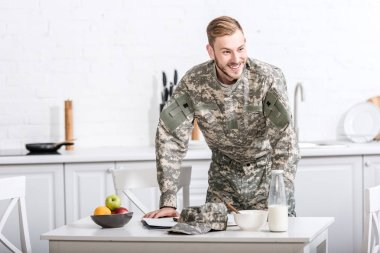 Army soldier at kitchen table having breakfast stock vector