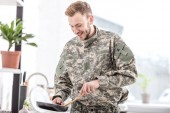 Fotografie smiling army soldier cooking on pan in kitchen