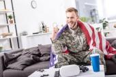vzrušený, voják armády pod americkou vlajkou sedí na gauči, fandění a a sledoval fotbalový zápas doma