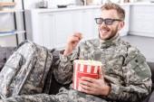 usmívající se voják ve vojenské uniformě, 3d brýle, jíst popcorn a sledování filmu na gauči