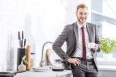 Fotografie smiling businessman drinking coffee in kitchen and looking at camera