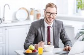 businessman working on laptop while eating breakfast at kitchen