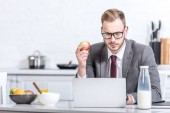 businessman working on laptop while eating apple at kitchen