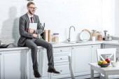 podnikatel, sedí na desce a držení notebooku v kuchyni doma