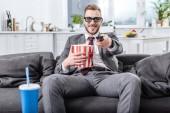 Fotografie gut aussehend Geschäftsmann auf Couch in 3d Brille mit Fernbedienung Film und Essen popcorn