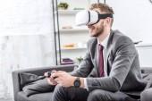 Lächelnder Geschäftsmann mit Virtual-Reality-Headset und Videospiel auf der heimischen Couch