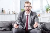aufgeregt Geschäftsmann hält Konsole und Spiel zu Hause video
